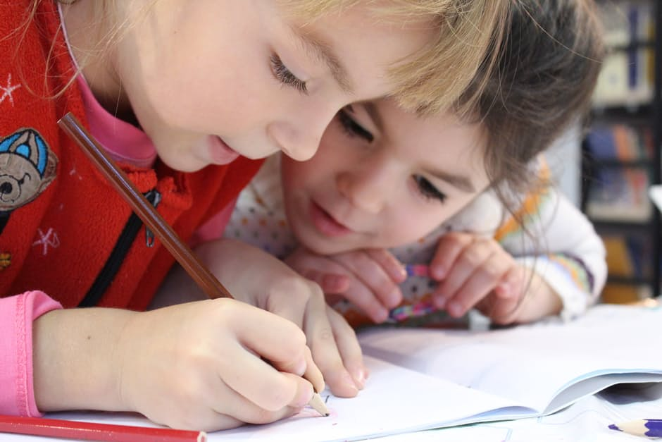 A closeup of two little girls' faces while one writes on a piece of paper.