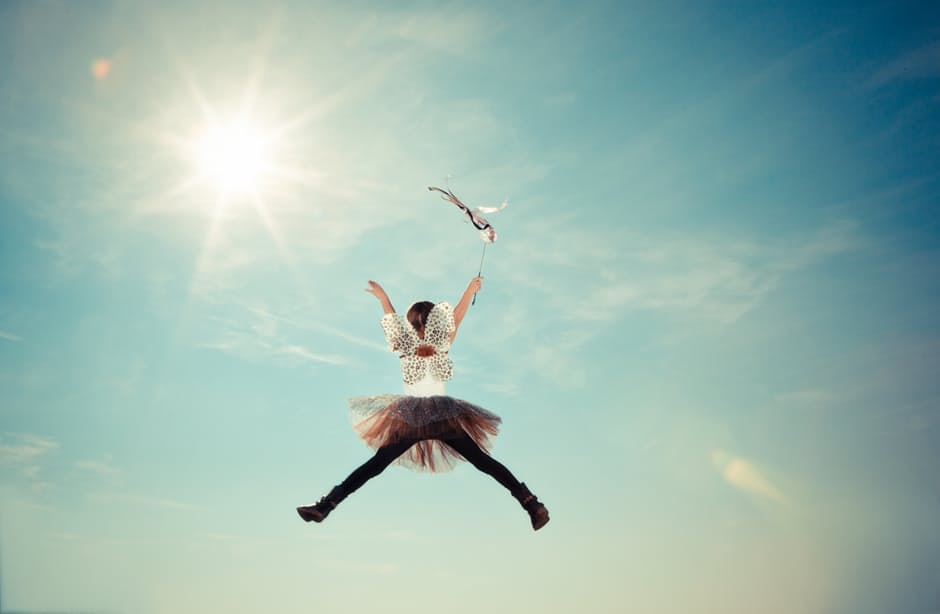 The back of a young girl jumping up in a star pose with the sun and the blue sky being the background. She has a fairy costume on with wings and a tutu.
