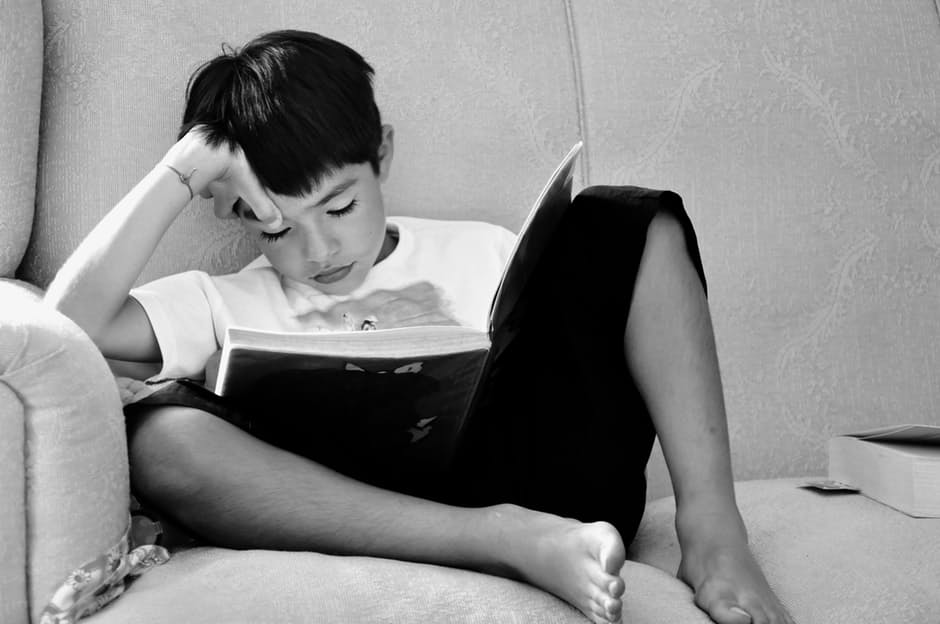 A black and white photo of a boy sitting on a couch while reading. His head is leaning on one of his hands while the other holds the book which is also resting in between his knees.
