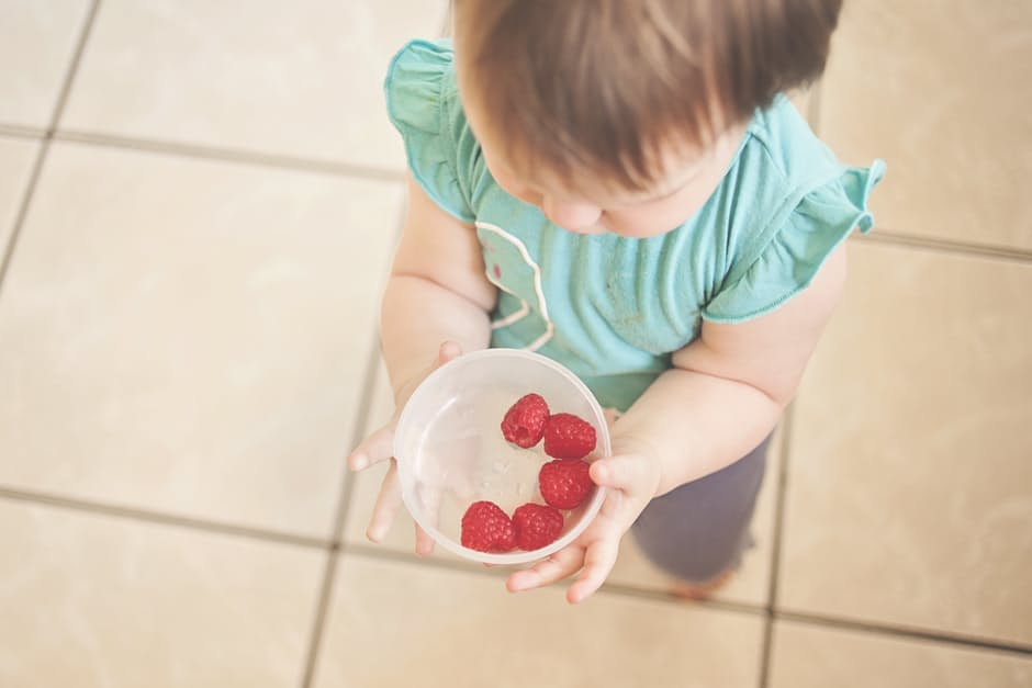 An arial view of a little girl in a blue shirt holding a bowl of raspberries