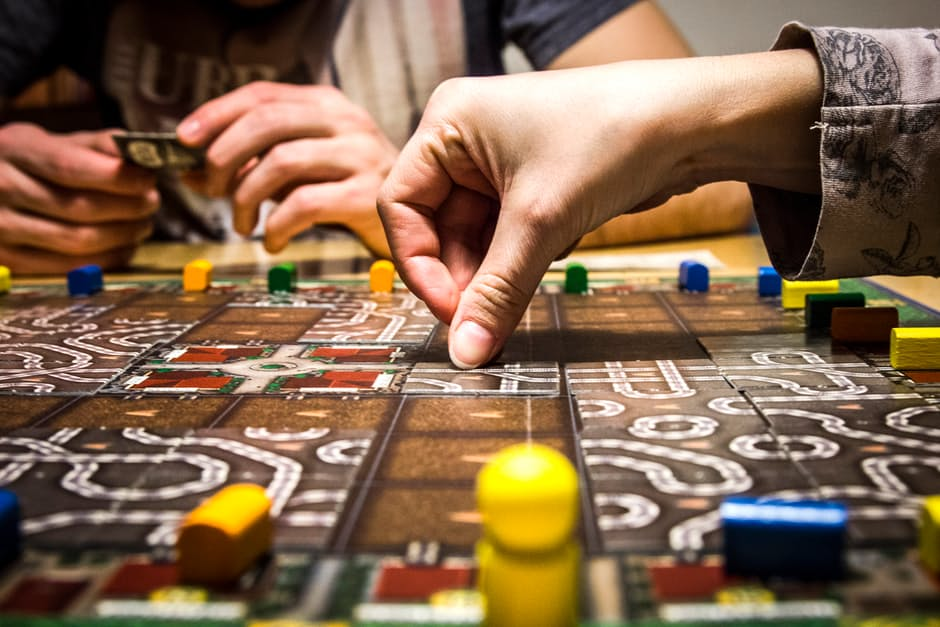 Close of hands playing a board game.