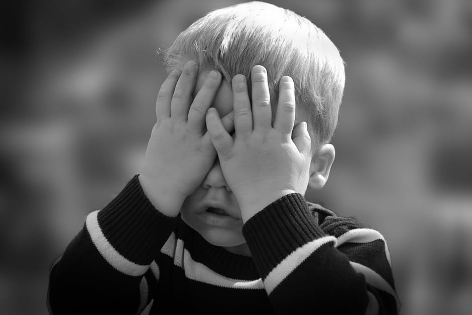 A black and white closeup of a little boy putting his hands over his eyes.